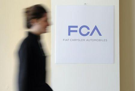 A woman walks past a logo of Fiat Chrysler Automobiles in Turin