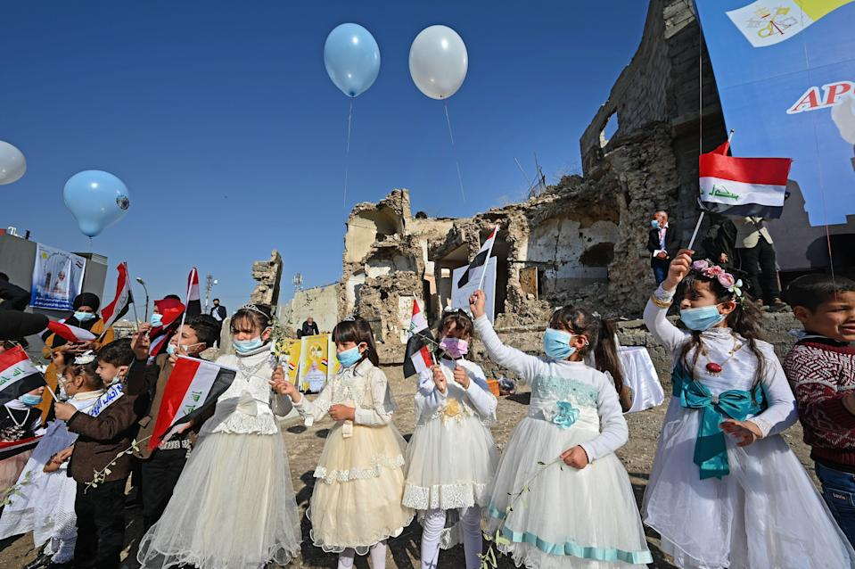 Iraqi children dressed in costumes wave national flags near the ruins of the Syriac Catholic Church of the Immaculate Conception, ahead of the Pope's visitAFP/Getty