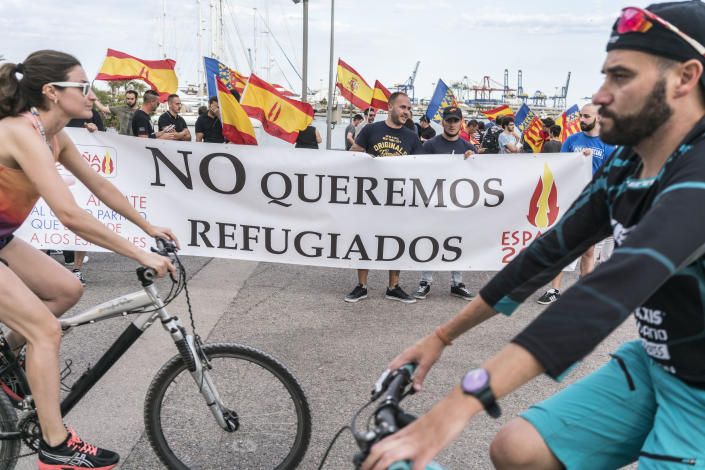 """<p>People gather holding a banner that reads """"We do not want refugees"""" at the port of Valencia. (Photo: José Colón for Yahoo News) </p>"""