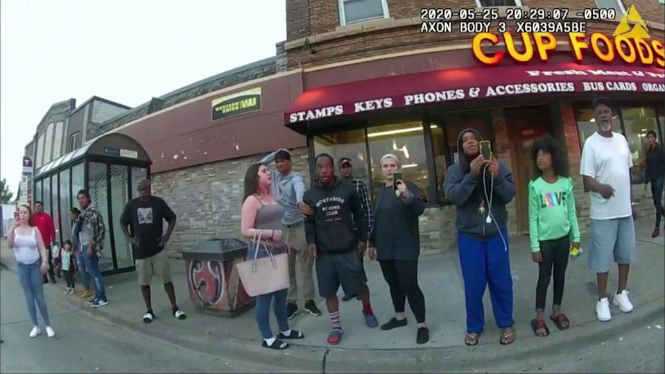 Police body camera footage shows bystanders watching police officer Derek Chauvin subdue George Floyd in Minneapolis, including Alyssa Funari, left, filming; Charles McMillian, center left in light-colored shorts; Christopher Martin, center in gray; Donald Williams, center in black; Genevieve Hansen, fourth from right, filming; and Darnella Frazier, third from right, filming.