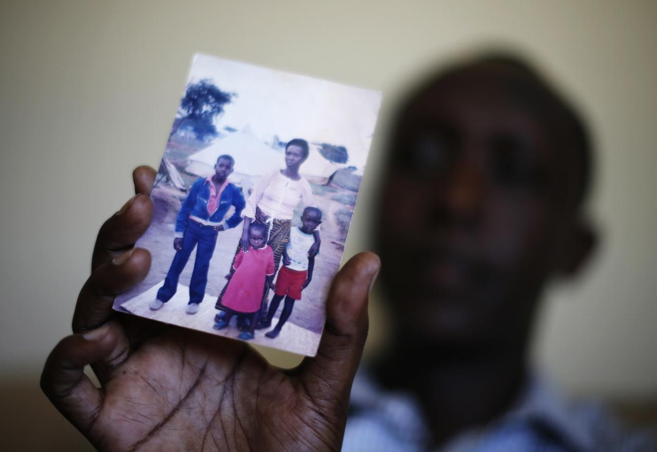 Patrick Manyika, 33, of Rwanda holds up a photo of himself (R), his mother, brother and sister, in Redlands, California May 14, 2014. Manyika was born in a Ugandan refugee camp after his Tutsi family fled Rwanda. In 1983, unrest forced them back to Rwanda, where they lived first in a national park, then in the capital. Manyika survived the Rwandan genocide of 1994, in which 800,000 Tutsis and moderate Hutus were killed, by sheltering in a UN-controlled soccer stadium. After doing charity work and teaching himself various languages, in 2009 he had the opportunity to leave Rwanda and pursue his education in the United States. He is now about to start his second Masters degree. June 20 is World Refugee Day, an occasion that draws attention to those who have been displaced around the globe. In the run-up to the date, Reuters photographers in different regions have photographed various people who have at some point fled their homes. Picture taken May 14, 2014. REUTERS/Lucy Nicholson (UNITED STATES - Tags: SOCIETY IMMIGRATION POLITICS)
