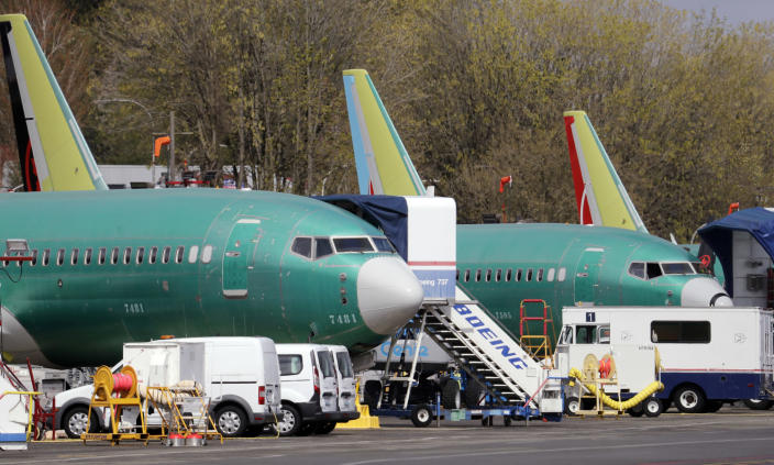 FILE - In this Monday, April 8, 2019, file photo, Boeing 737 Max 8 jets, built for American Airlines, left, and Air Canada are parked at the airport adjacent to a Boeing Co. production facility in Renton, Wash. Orders and deliveries of Boeing's 737 Max plunged in the first quarter as the plane was grounded around the world following a second deadly crash. Boeing disclosed Tuesday, April 9, that it received no new orders for the Max in March. (AP Photo/Elaine Thompson, File)