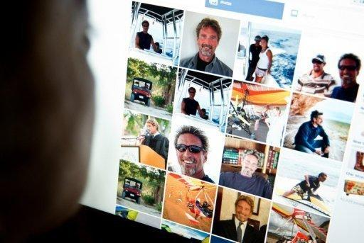 A woman looks at software pioneer John McAfee's facebook page