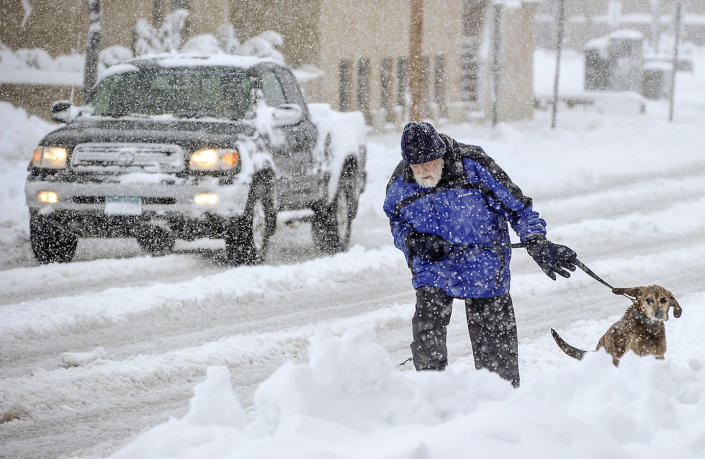 Mike Gregg trudges through the snow to walk his dog, Jake, in Austin, Minn., Thursday morning, May 2, 2013. Winter made a return appearance in southeastern Minnesota, where residents are digging out of more than a foot of heavy, wet snow. (AP Photo/Austin Daily Herald, Eric Johnson)