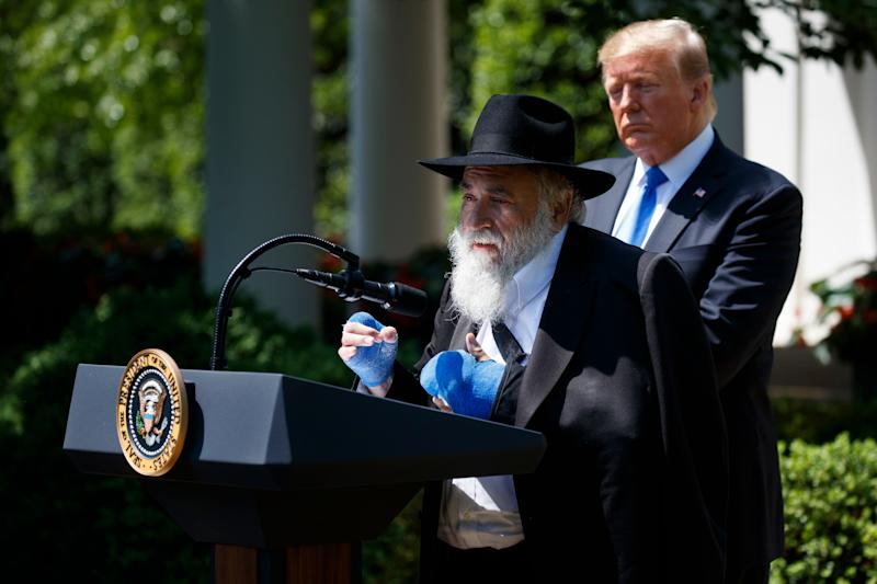 President Donald Trump looks on as Rabbi Yisroel Goldstein, survivor of the Poway, Calif., synagogue shooting, speaks during a National Day of Prayer event in the Rose Garden of the White House.