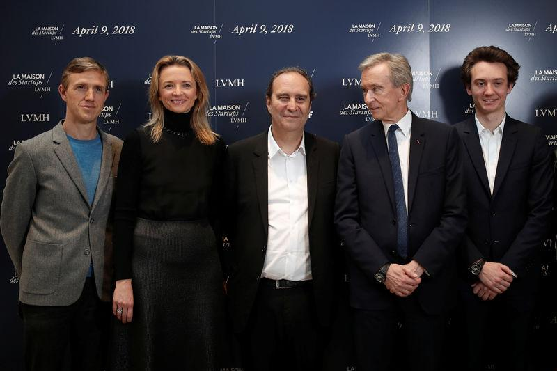 "Ian Rogers, Delphine Arnault, Xavier Niel, Bernard Arnault, Frederic Arnault pose for a photograph at ""Station F"", a mega-campus for startups located inside a former freight railway depot in Paris"