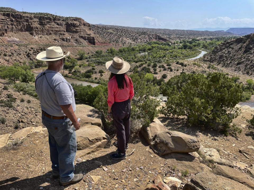 This Aug. 31, 2021 photo shows U.S. Rep. Teresa Leger Fernández, center, surveying the Rio Chama valley near Abiquiu, New Mexico, as Tim Seaman with the Rio Chama Acequia Association looks on. The traditional irrigation systems known as acequias are feeling more pressure as drought persists and climate change piles on with warmer temperatures. (AP Photo/Susan Montoya Bryan)