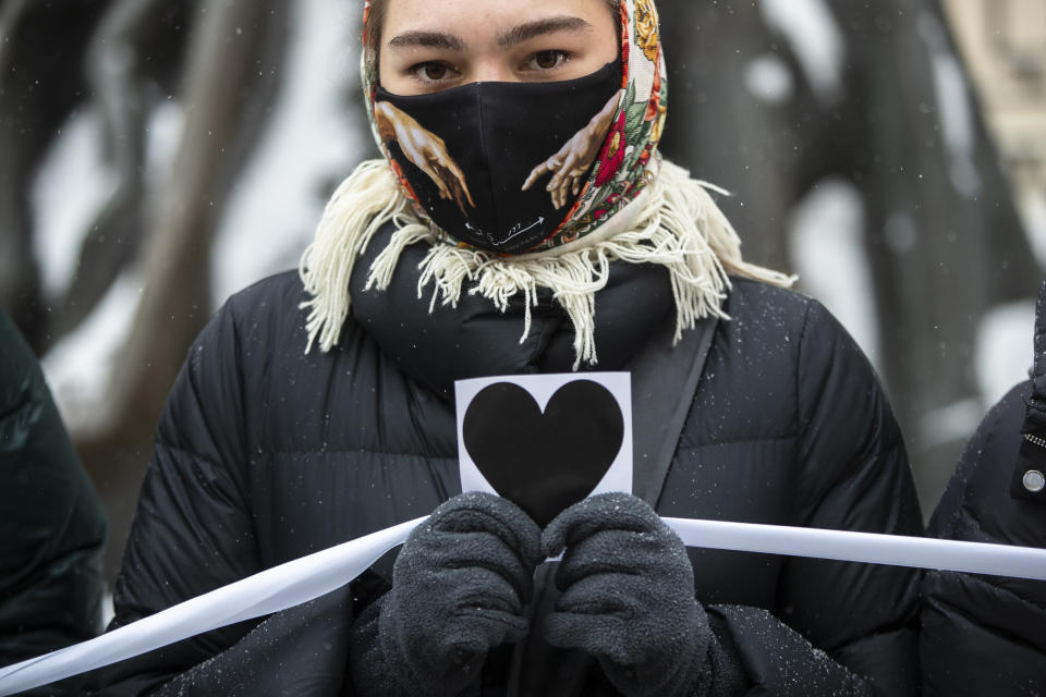 A woman holds an image of heart and a white ribbon as she stands in a line of women during a rally in support of jailed opposition leader Alexei Navalny and his wife Yulia Navalnaya at Arbat street in Moscow, Russia, Sunday, Feb. 14, 2021. (AP Photo/Pavel Golovkin)