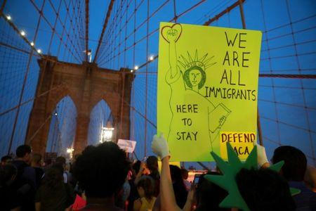 People march across the Brooklyn Bridge to protest the planned dissolution of DACA in Manhattan, New York City, U.S.