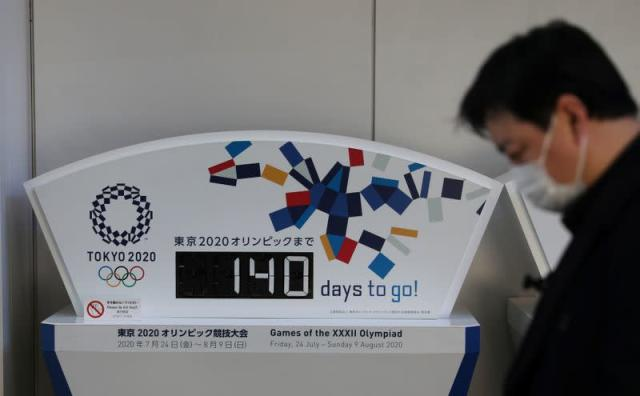 A man wearing a protective face mask, following an outbreak of the coronavirus, walks past a countdown clock for the opening ceremony of the Tokyo 2020 Olympic Games in Tokyo