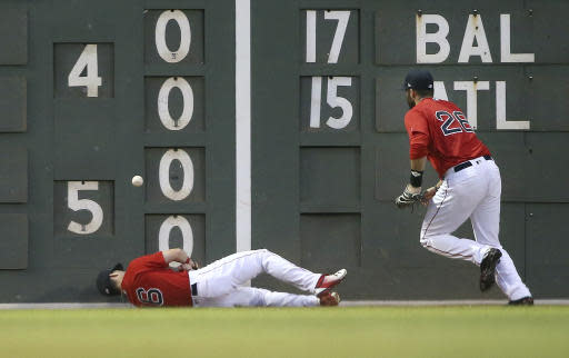 Boston Red Sox center fielder Andrew Benintendi (16) falls after crashing into the wall as left fielder J.D. Martinez (28) chases down an RBI-double by Seattle Mariners' Denard Span in the fourth inning of a baseball game at Fenway Park, Friday, June 22, 2018, in Boston. (AP Photo/Elise Amendola)