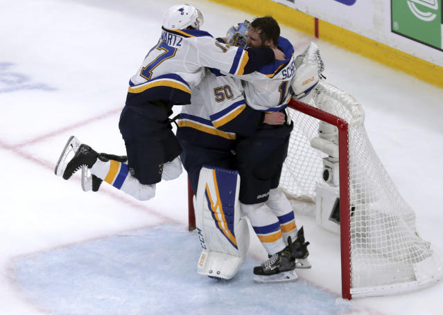 St. Louis Blues' Jaden Schwartz, left, and Brayden Schenn, right, mob goaltender Jordan Binnington, to celebrate their win over the Boston Bruins in Game 7 of the NHL hockey Stanley Cup Final, Wednesday, June 12, 2019, in Boston. (AP Photo/Charles Krupa)