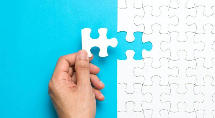 A hand putting the last piece of a white puzzle in place against a blue backdrop.
