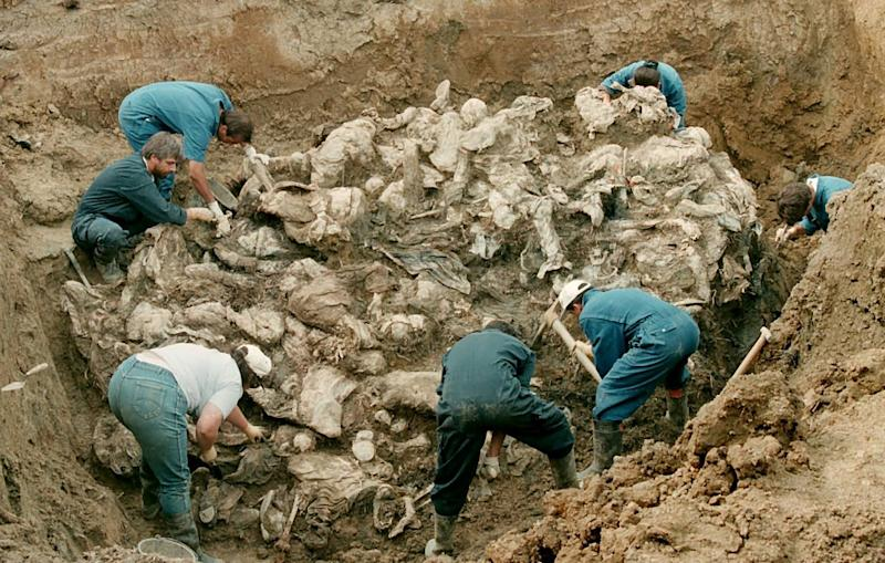 Forensic experts from the International war crimes tribunal in the Hague work on a pile of partly decomposed bodies, July 24, 1996 found in a mass grave in the village of Pilica some 300 km northeast of Sarajevo (AFP Photo/Odd Andersen)