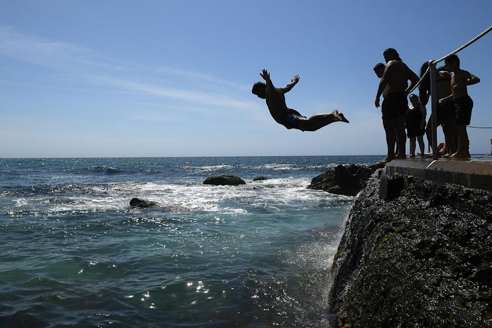Boys jump from rocks into ocean.