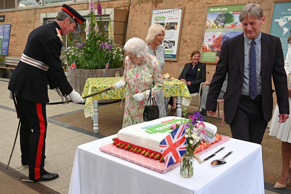 ST AUSTELL, ENGLAND - JUNE 11: Queen Elizabeth II (C) takes a sword from The Lord-Lieutenant of Cornwall, Edward Bolitho (L) in order to cut a cake to celebrate of The Big Lunch initiative at The Eden Project during the G7 Summit on June 11, 2021 in St Austell, Cornwall, England. UK Prime Minister, Boris Johnson, hosts leaders from the USA, Japan, Germany, France, Italy and Canada at the G7 Summit. This year the UK has invited India, South Africa, and South Korea to attend the Leaders' Summit as guest countries as well as the EU. (Photo by Oli Scarff - WPA Pool / Getty Images)