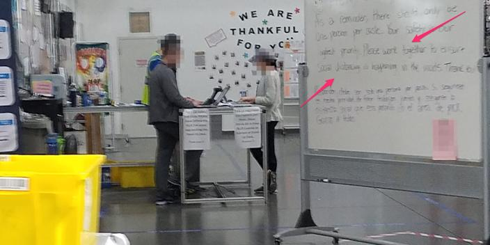 Employees at an Amazon warehouse in Indiana huddle for a meeting next to signs encouraging employees to stay apart.