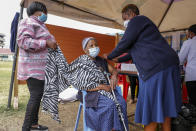 A Kenyan woman receives the AstraZeneca coronavirus vaccine at Kenyatta National Hospital in Nairobi, Kenya Thursday, Aug. 26, 2021. Wealthier nations are awash in vaccines, while they are scarce in poorer countries and many people are still waiting for their first shot. (AP Photo/Brian Inganga)