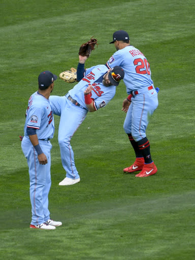 Minnesota Twins center fielder Jake Cave, center, collides with left fielder Eddie Rosario, right, as Rosario catches a fly ball hit by Cincinnati Reds' Curt Casali as shortstop Jorge Polanco, left,looks on during the fifth inning of a baseball game Sunday, Sept. 27, 2020, in Minneapolis. (AP Photo/Craig Lassig)