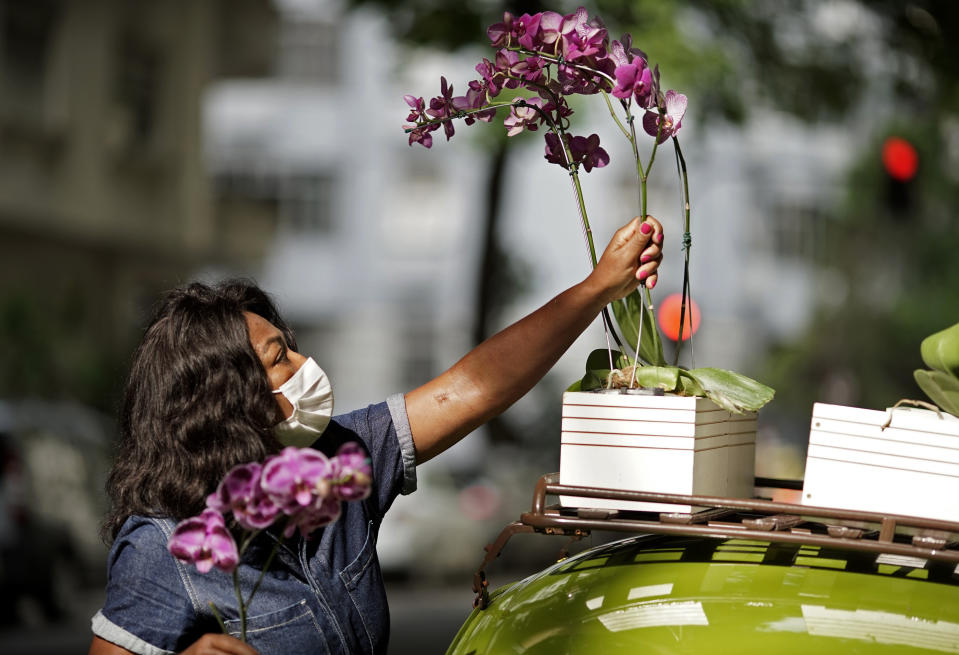 Roberta Machado arranges flowers on her 1969 VW beetle in the Copacabana neighborhood of Rio de Janeiro, Brazil, Wednesday, Oct. 21, 2020. After she saw her business of renting rooms for tourists dry up due to the COVID-19 pandemic, she converted her car into a mobile flower shop. (AP Photo/Silvia Izquierdo)