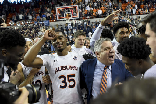 Auburn head coach Bruce Pearl celebrates with players after a win over Tennessee in an NCAA college basketball game Saturday, Feb. 22, 2020, in Auburn, Ala. (AP Photo/Julie Bennett)