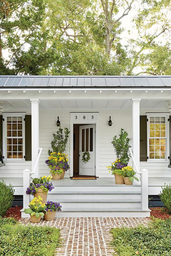 """<p>The homeowner widened and deepened the front stoop, turning it into a porch that's 28 by 8 feet. Rather than crowd the porch with furniture, dueling porch swings were hung and guests are encouraged to pull out chairs.</p> <p><a rel=""""nofollow"""" href=""""http://www.southernliving.com/home/remodel/tiny-house-design-tips"""">Tour the 660-square-foot cottage.</a></p>"""