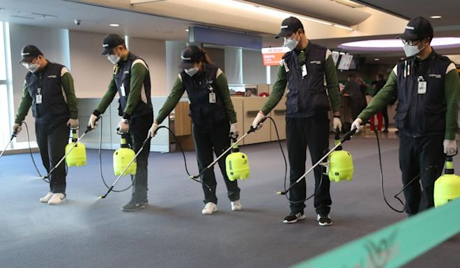 Workers from a cleaning service spray disinfectant at the customs, immigration and quarantine area at Incheon international airport, west of Seoul, on Tuesday, after South Korea confirmed its first case of Wuhan coronavirus. Photo: Yonhap via AFP