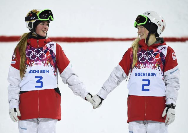 Second-placed Chloe Dufour-Lapointe (L) of Canada and her sister, first-placed Justine Dufour-Lapointe (R), hold hands during the flower ceremony for the women's freestyle skiing moguls event at the 2014 Sochi Winter Olympic Games in Rosa Khutor, February 8, 2014. REUTERS/Dylan Martinez (RUSSIA - Tags: SPORT SKIING OLYMPICS TPX IMAGES OF THE DAY)