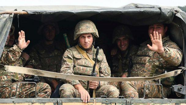 PHOTO: Servicemen of Karabakh's Defence Army wave while riding in the back of a truck on the way to the town of Martakert during fighting with Azerbaijan over the breakaway Nagorny Karabakh region, Sept. 29, 2020.  (Narek Aleksanyan/AFP via Getty Images)