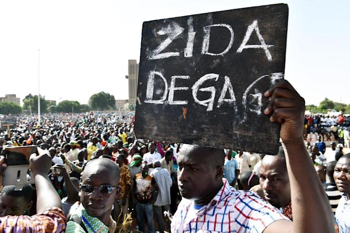 """A man holds up a sign that reads """"Zida get out"""" in French, referring to Isaac Zida, an officer named by the military to lead the country's transition, during a protest in Ouagadougou, Burkina Faso, on November 2, 2014 (AFP Photo/Issouf Sanogo)"""