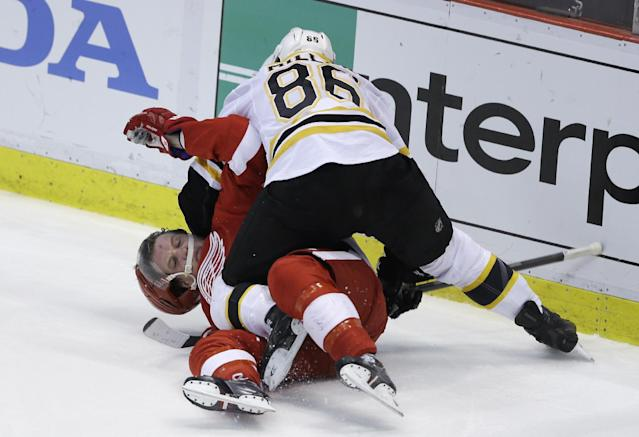 Boston Bruins defenseman Kevan Miller (86) takes down Detroit Red Wings left wing Justin Abdelkader (8) and is called for roughing during the second period of Game 4 of a first-round NHL hockey playoff series in Detroit, Thursday, April 24, 2014. (AP Photo/Carlos Osorio)