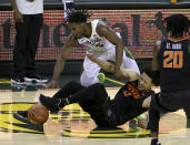 Oklahoma State guard Cade Cunningham (2) injures his ankle as he and Baylor guard Davion Mitchell (45) reach for the loose ball in the second half of an NCAA college basketball game, Thursday, March 4, 2021, in Waco, Texas. (AP Photo/Jerry Larson)