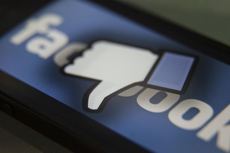 Facebook thumbs-down hand on a iPhone. Facebook is a social media company owned by Mark Zuckerberg. Photo: Ted Soqui/Corbis via Getty Images