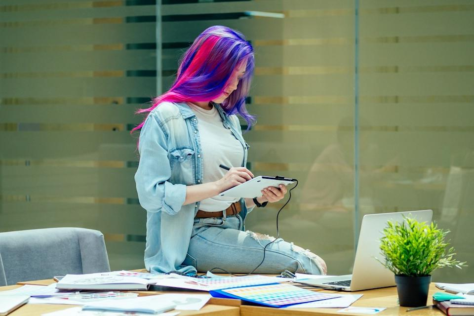 woman with colorful hair wearing ripped jeans