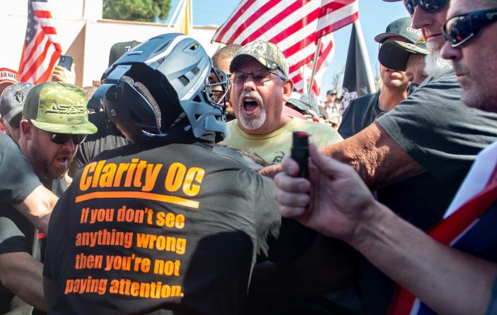Black Lives Matter protesters and counter protesters clash in Yorba Linda, Calif., Saturday, Sept. 26, 2020. Police eventually declared the event an unlawful gathering and cleared the streets near Yorba Linda and Imperial. Authorities said people were struck by a car and injured during a Black Lives Matter protest and counter-protest about 30 miles southeast of Los Angeles. Orange County Sheriff's Department spokeswoman Carrie Braun says the injured were transported to a hospital with non-life-threatening injuries and the driver was detained. (Mindy Schauer/The Orange County Register via AP)