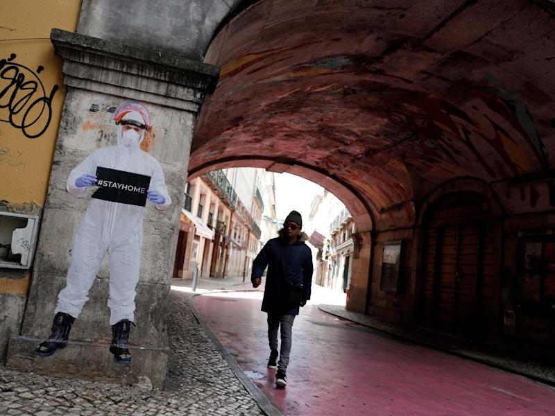 A man walks next to a picture of photographer Salvador Colaco in downtown Lisbon: Reuters