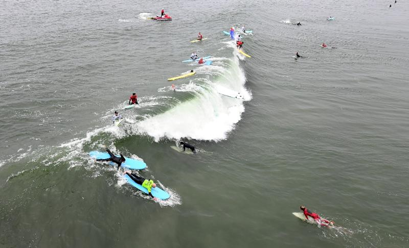 US military veterans, assisted by surf volunteers, catch waves at the Operation Surf event on June 4, 2019 in Huntington Beach, California (AFP Photo/Frederic J. BROWN)