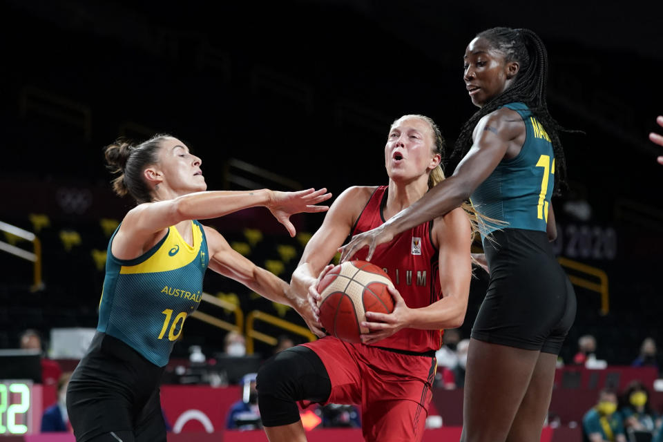 Belgium's Julie Allemand, center, drives to the basket between Australia's Katie Ebzery (10) and Ezi Magbegor, right, during a women's basketball preliminary round game at the 2020 Summer Olympics, Tuesday, July 27, 2021, in Saitama, Japan. (AP Photo/Charlie Neibergall)