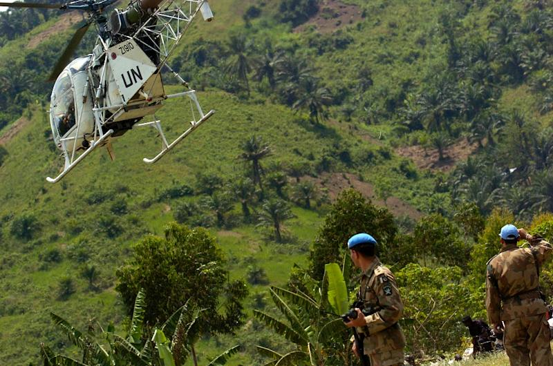 UN peacekeeping forces watch a UN helicopter take off from an airstrip at Bunyakiri base in South Kivu province, DR Congo on February 25, 2006