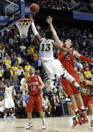 Marquette guard Vander Blue (13) scores the game-winning basket against Davidson forward Jake Cohen (15) in the final seconds of a second-round NCAA college basketball tournament game Thursday, March 21, 2013, in Lexington, Ky. Marquette won 59-58. (AP Photo/John Bazemore)