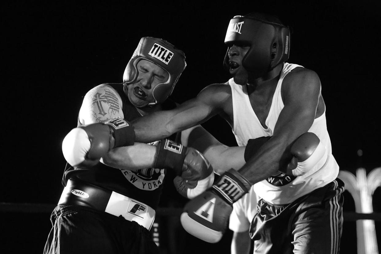 """Nick Albergo, left, take one on the chin from Paul Maurice during a grudge match at the """"Brooklyn Smoker"""" boxing event in the parking lot of Gargiulo's Italian Restaurant in Coney Island, Brooklyn, on Aug. 24, 2017. Maurice won the three-round bout. (Photo: Gordon Donovan/Yahoo News)"""
