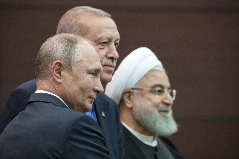 Russian President Vladimir Putin, left, Turkish President Recep Tayyip Erdogan and Iranian President Hassan Rouhani, right, pose for a picture after a news conference during their meeting in Ankara, Turkey, Monday, Sept. 16, 2019. The leaders of Russia, Iran and Turkey met in the Turkish capital to discuss the situation in Syria, with the aim of halting fighting in the northwest of the country and finding a lasting political solution to the 8 1/2 year civil war. (AP Photo/Pavel Golovkin, Pool)