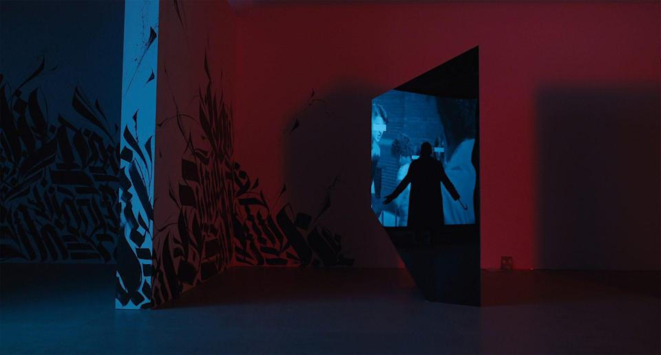 Candyman character stands in art gallery in dark with flashes of red and blue lights