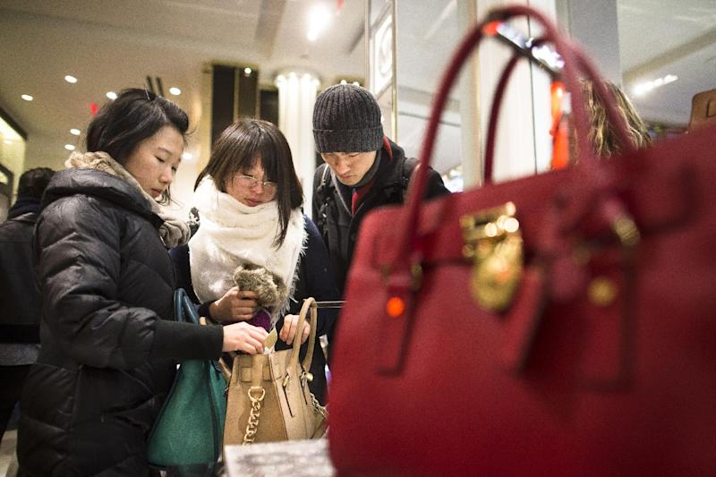 Shoppers inspect a handbag at the Macy's Herald Square flagship store, Thursday, Nov. 28, 2013, in New York. Instead of waiting for Black Friday, which is typically the year's biggest shopping day, more than a dozen major retailers are opening on Thanksgiving this year. (AP Photo/John Minchillo)