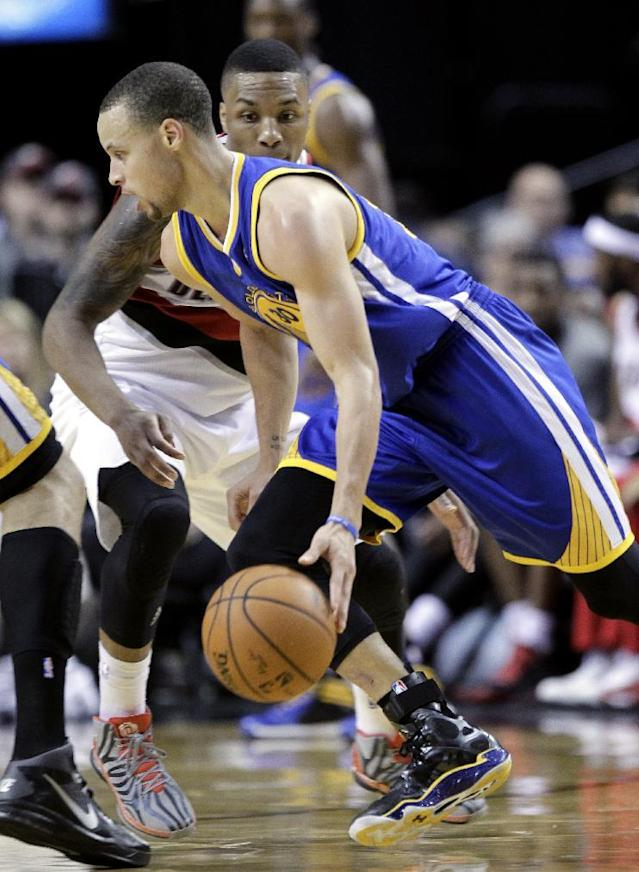 Golden State Warriors guard Stephen Curry, left, drives on Portland Trail Blazers guard Damian Lillard during the second half of an NBA basketball game in Portland, Ore., Sunday, March 16, 2014. Curry led the Warriors with 37 points, six of them three point shots, to beat the Trail Blazers 113-112. (AP Photo/Don Ryan)