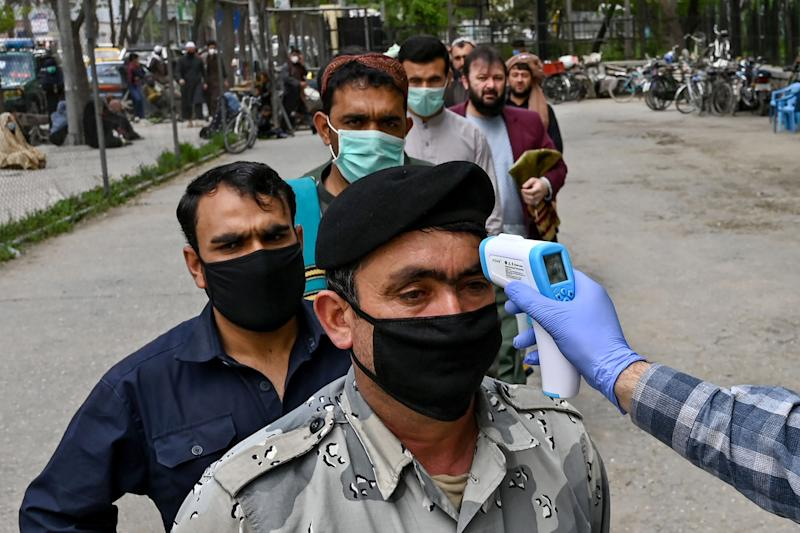 Image: A health worker checks the body temperature of a devotee as a preventive measure against the COVID-19 coronavirus before the Friday prayers on the first day of the Muslim holy month of Ramadan at Wazir Akbar Khan mosque (WAKIL KOHSAR / AFP - Getty Images file)