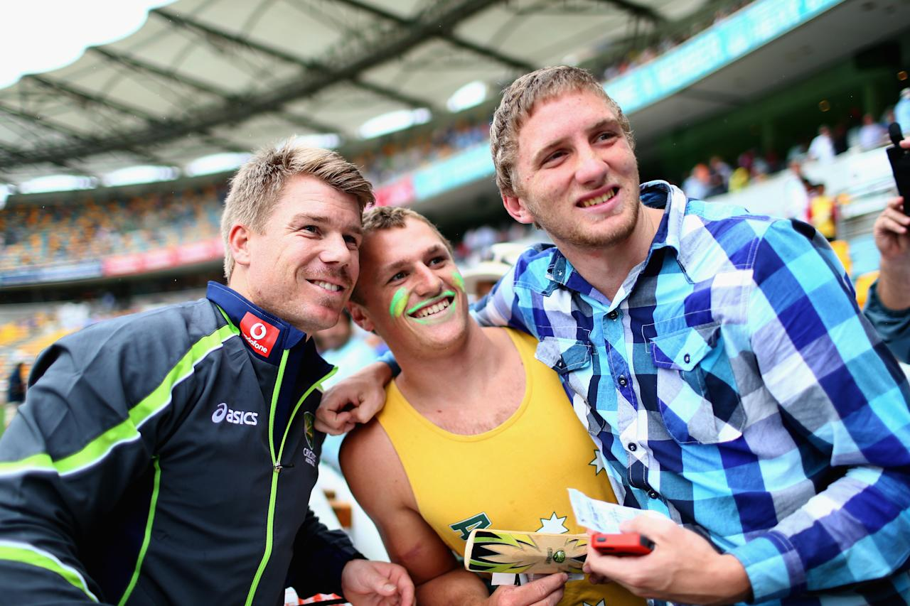 BRISBANE, AUSTRALIA - NOVEMBER 10:  David Warner of Australia poses with fans as rain delays the start of play during day two of the First Test match between Australia and South Africa at The Gabba on November 10, 2012 in Brisbane, Australia.  (Photo by Ryan Pierse/Getty Images)