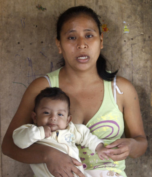 In this Wednesday, Feb. 12, 2014 photo, Irma Lopez, holding her son Sabino Slavador, talks during a interview in her house in San Felipe Jalapa de Diaz, Mexico. Irma's plight garnered national attention last year when a photo showed the 29-year-old woman of Mazatec ethnicity squatting in pain immediately after giving birth in October on the lawn outside the Rural Health Center of the village of San Felipe Jalapa de Diaz. Lopez, and her son, Sabino Salvador, survived with no health problems, but the picture upset many Mexicans when it was widely shared on Twitter and Facebook and shown on the front pages of some national dailies. (AP Photo/Luis Alberto Cruz)