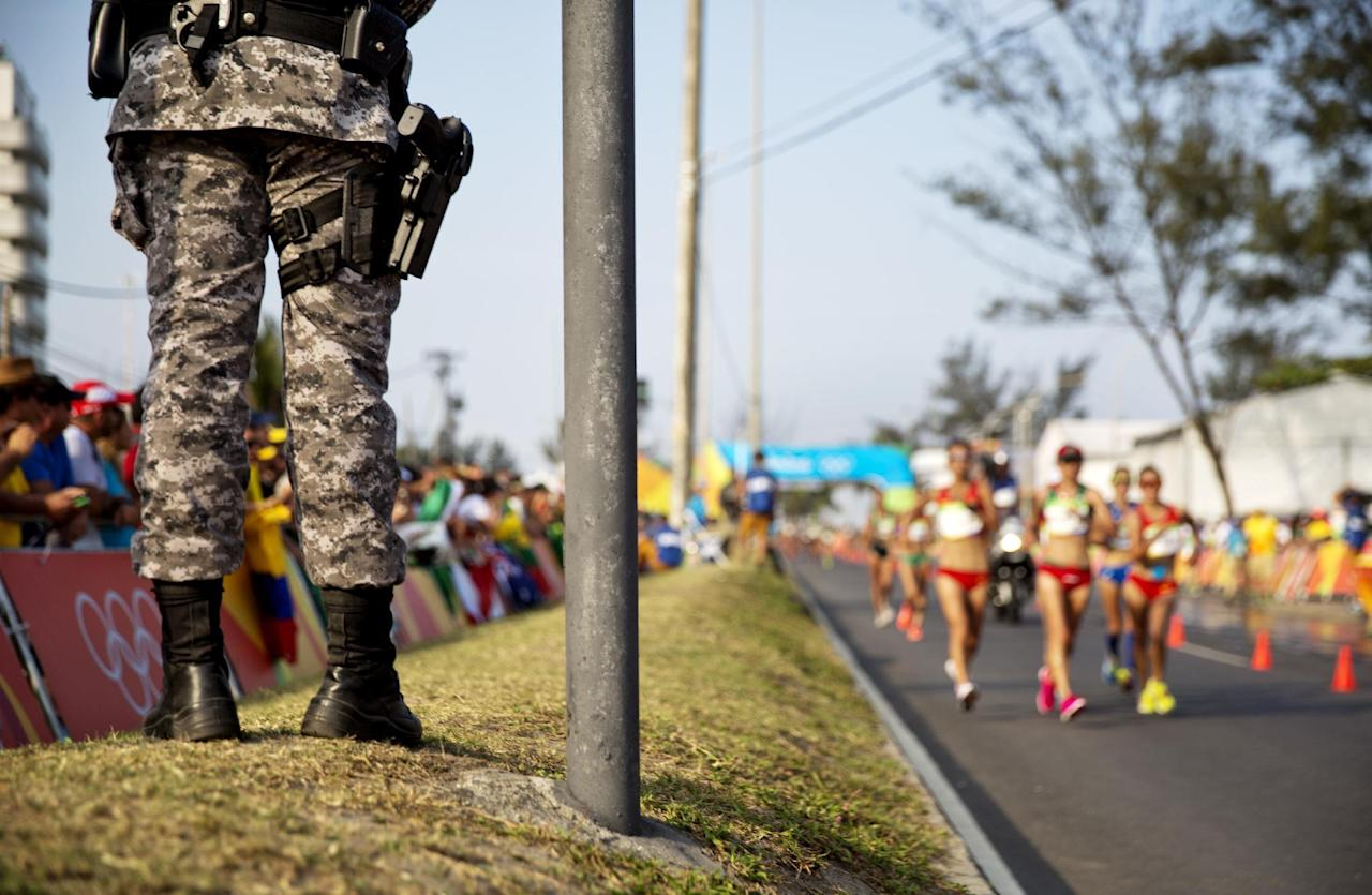 A National Security Force officer stands watch as the leaders pass by during the women's 20-km race walk at the 2016 Summer Olympics in Rio de Janeiro, Brazil, Friday, Aug. 19, 2016. (AP Photo/David Goldman)