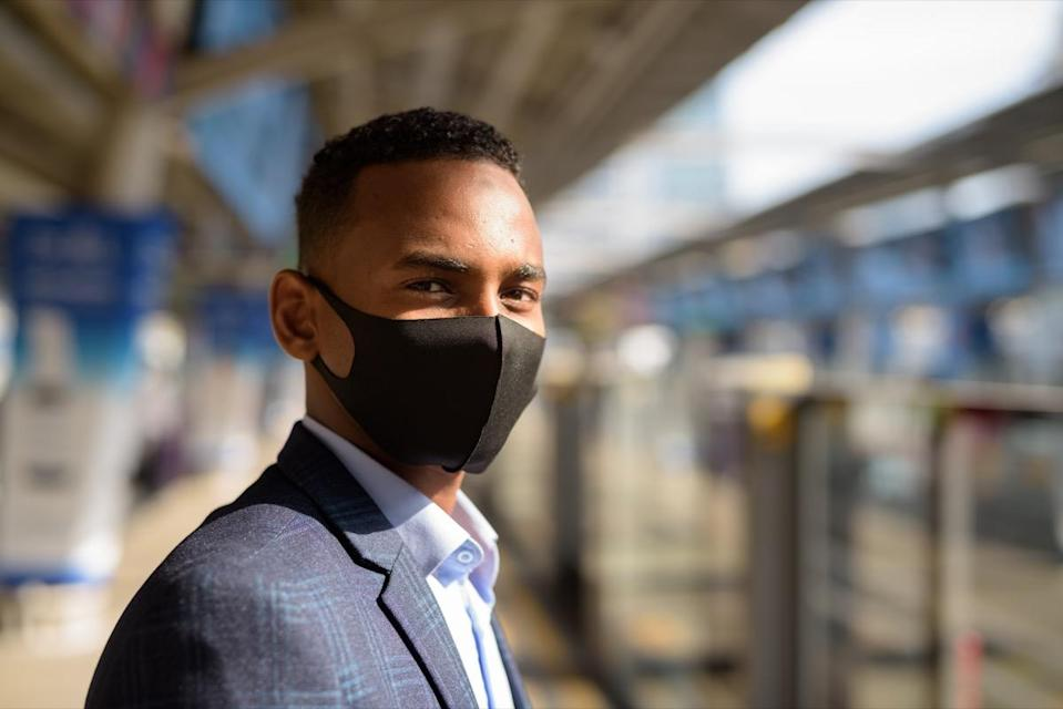 Portrait of young man with mask for protection from corona virus outbreak at the sky train station
